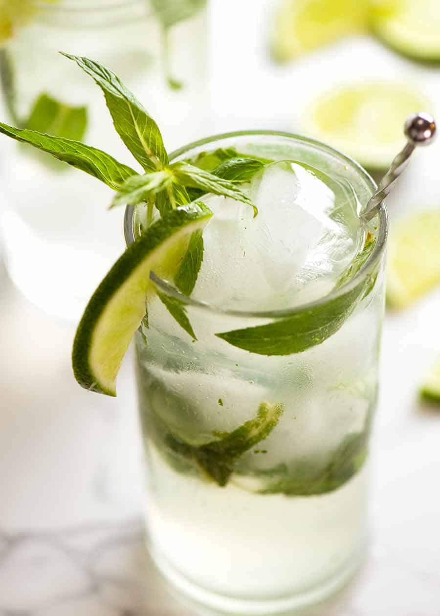 Close up photo of freshly made Mojito in a glass garnished with lime slice and fresh mint