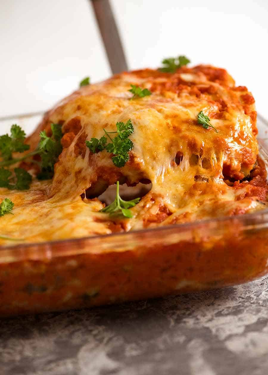 Cheese pull shot serving Spinach Beef Cannelloni from baking dish, fresh out of the oven