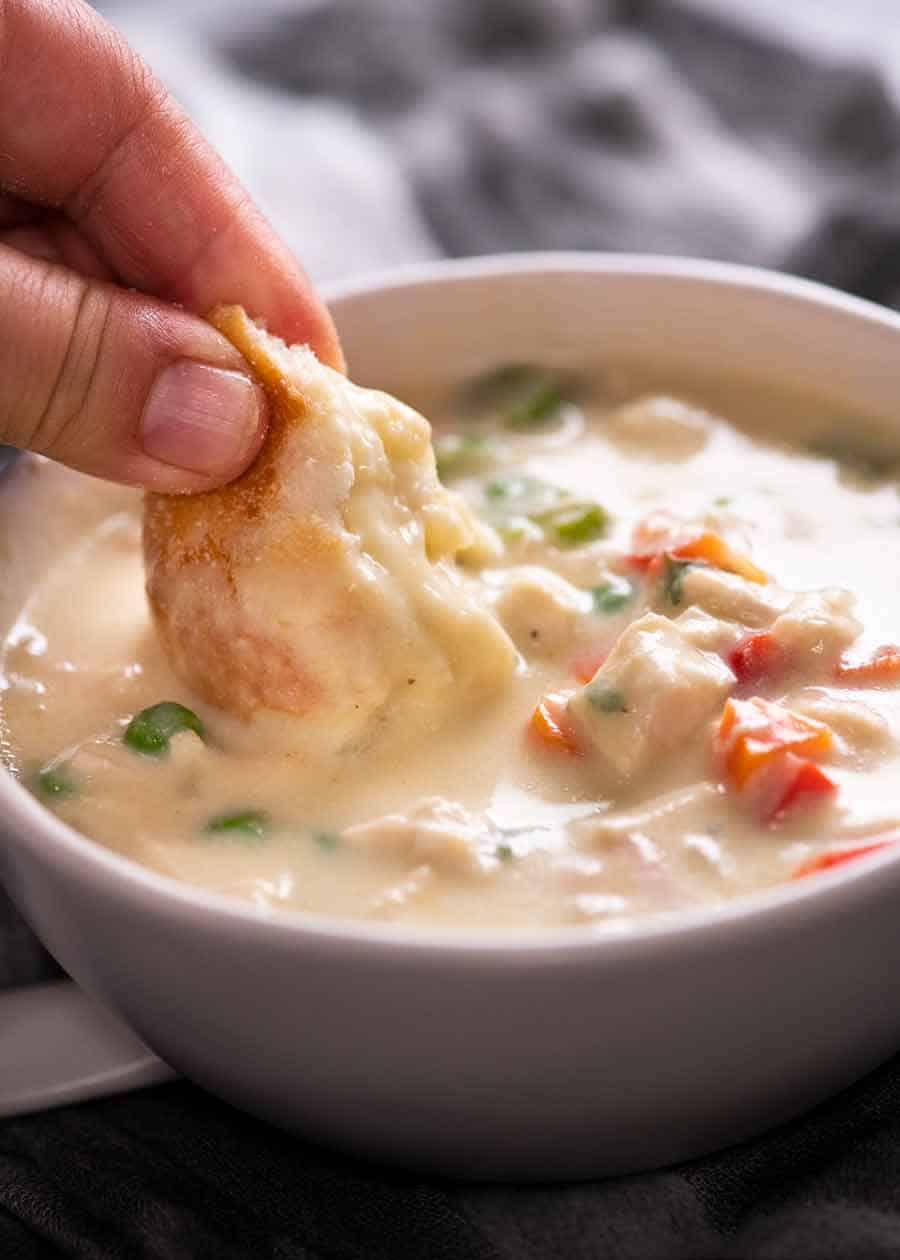 Close up of dunking bread into healthy Cream of Chicken Soup