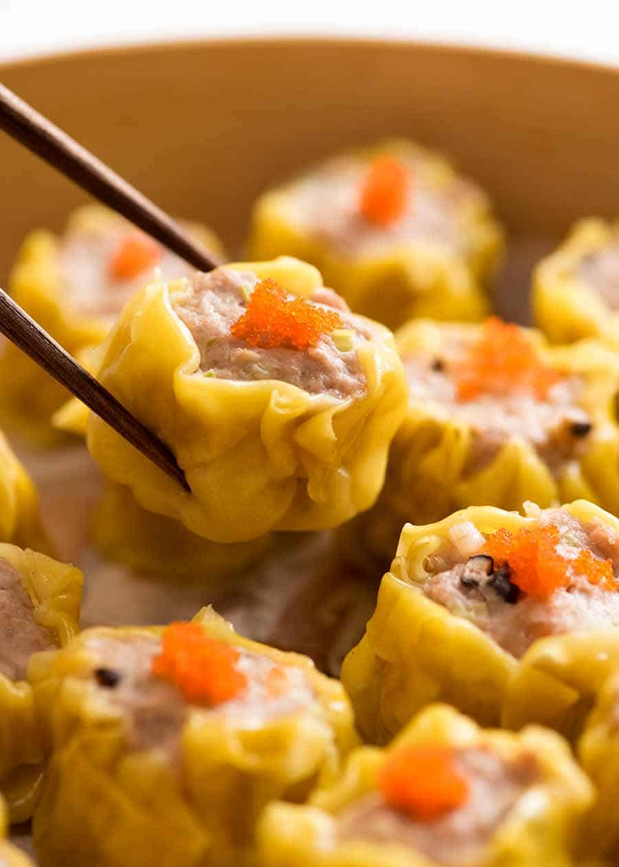 Close up of chopsticks holding Siu Mai (Chinese steamed dumpling) dipped in sauce